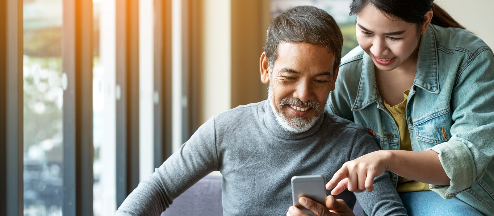 Smile attractive stylish short beard mature asian man using smartphone with young woman. Daughter teach asian old man or dad using internet social media network technology with digital gadget at home.