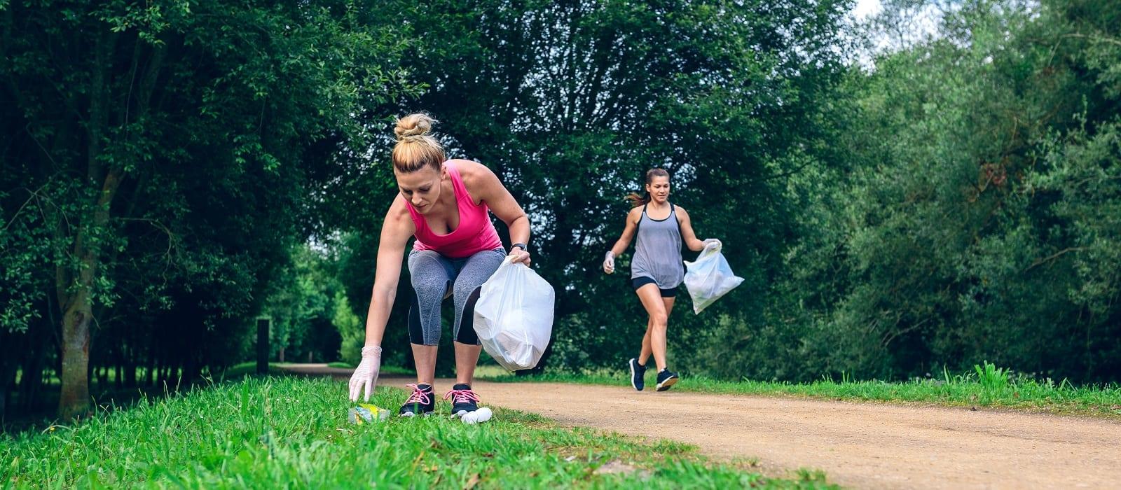 Two girls picking up trash while plogging outdoors