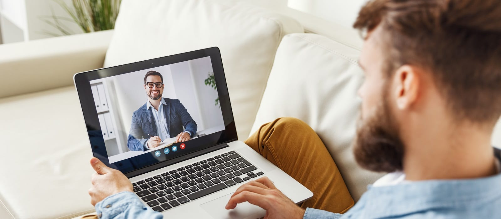 Modern  male sitting on couch and making video call to man financial consultant at home
