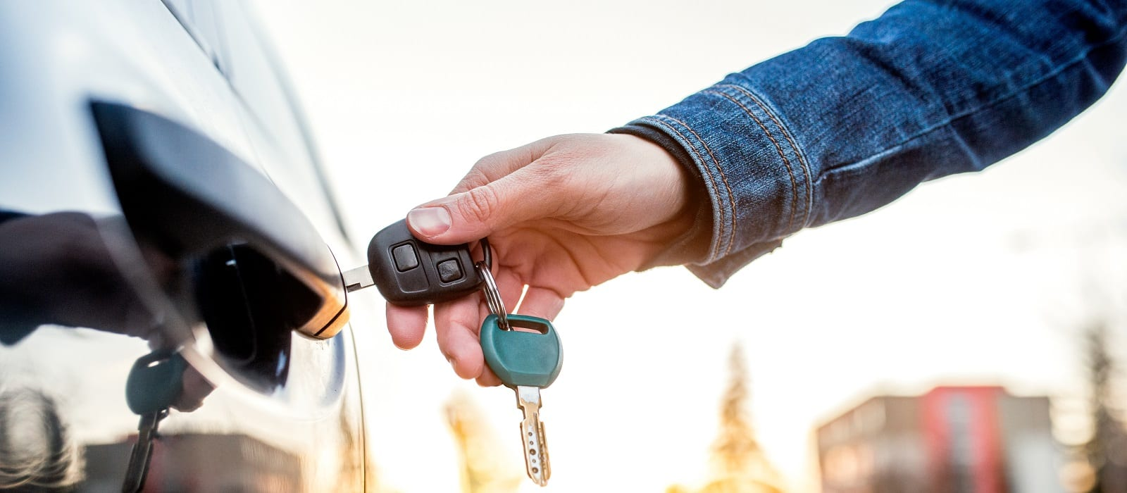 Unrecognizable woman opening her car with a key