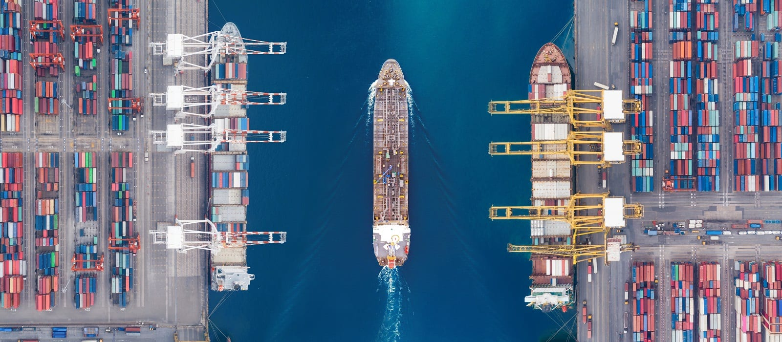 Aerial view panoramic oil tanker moving pass sea port warehouse and container ship or crane ship working for delivery containers shipment. Suitable use for energy power or transport or import export to global logistics concept.
