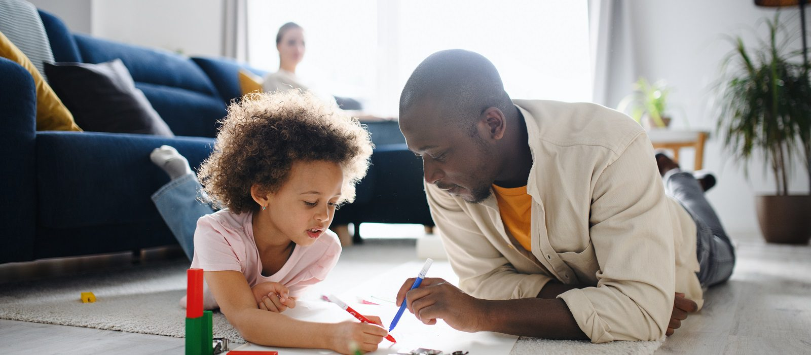 Father with small daughter drawing pictures, multi ethnic family and home office concept.