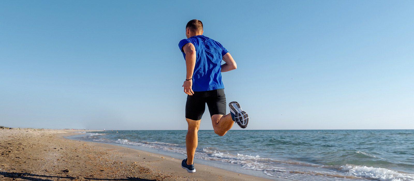 back man athlete running on sandy beach background blue sky