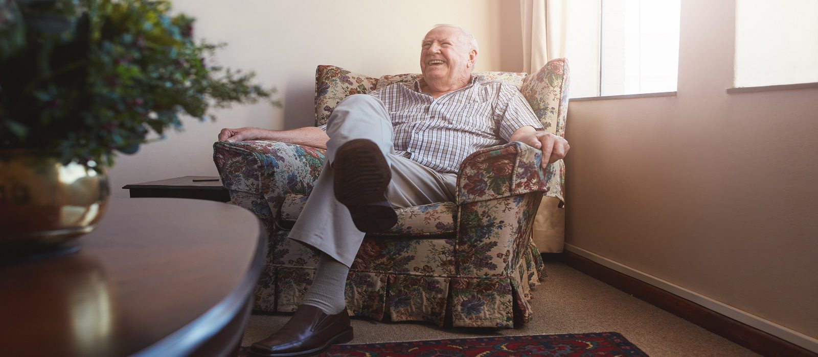 Indoor shot of smiling elderly man sitting on an arm chair at old age home.